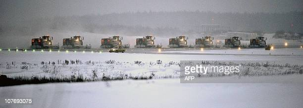 Eight snow ploughs clear the runway at the cargo terminal of Arlanda Airport in Stockholm on December 19 2010 Some flights were delayed or cancelled...
