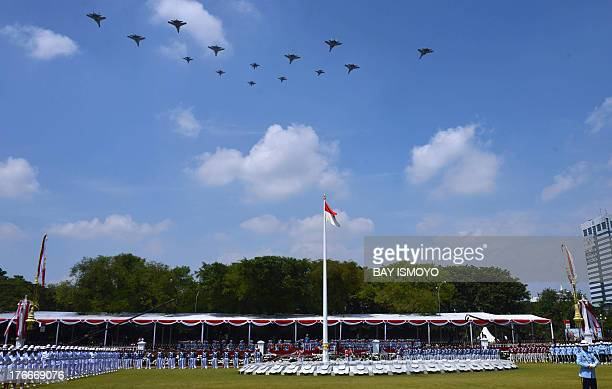 Eight Sukhoi and six F16 jet fighters fly over during the country's 68th independence day celebrations at the presidential palace in Jakarta on...