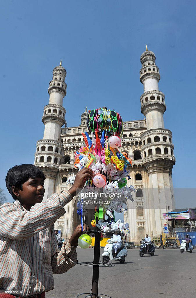 Eight year old Indian boy, Chandan Kumar arranges plastic toys on a stick for sale near the historic monument Charminar in the old city of Hyderabad on November 17, 2012. Restrictions were lifted on the movement of people and vehicular traffic around Charminar, where a mob indulged in stone pelting and trouble broke out after the noon prayers following the controversy over the newly erected structure near the Bhagyalaxmi temple. Muslims, supported by the Majlis-e-Ittehadul Muslimeen (MIM) party, opposed the move fearing that the temporary structure would pave the way for the permanent construction of a larger temple near the Charminar monument. AFP PHOTO / Noah SEELAM