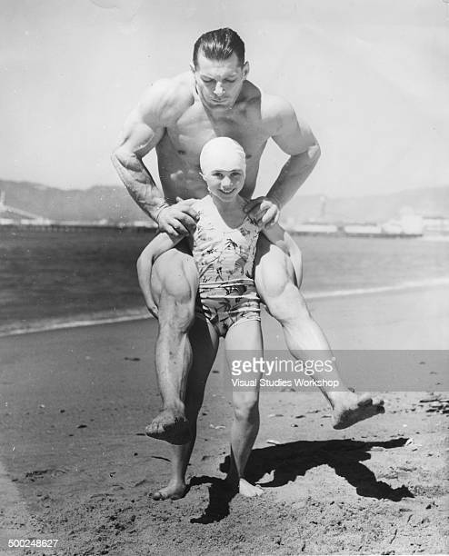 Eight year old Patricia O'Keefe weighing 64 pounds carrying Wayne Long her 200pound gymnastic partner on her back Venice California early to mid 20th...