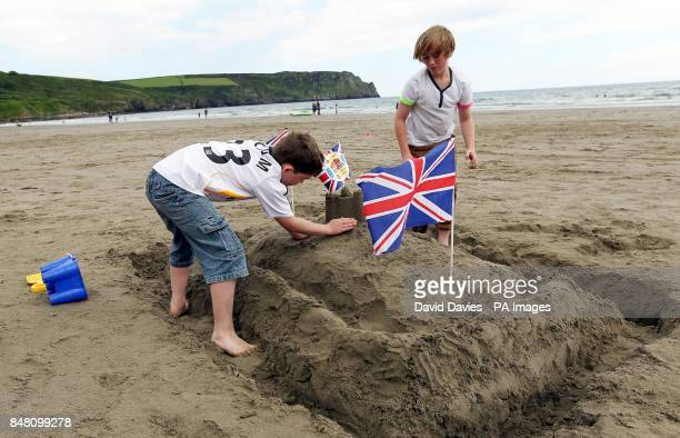 Eight year old Sam Davies and twelve year old Jack Davies from Worcester make their 'Jubilee Sand Castle' on Carne Beach in Cornwall
