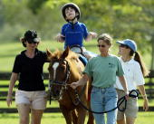 Eight yearold Michael DedrickDwyer who has Cerebral Palsy and Autism takes 30minute ride on a horse with therapist Rebecca Reubens and volunteer...