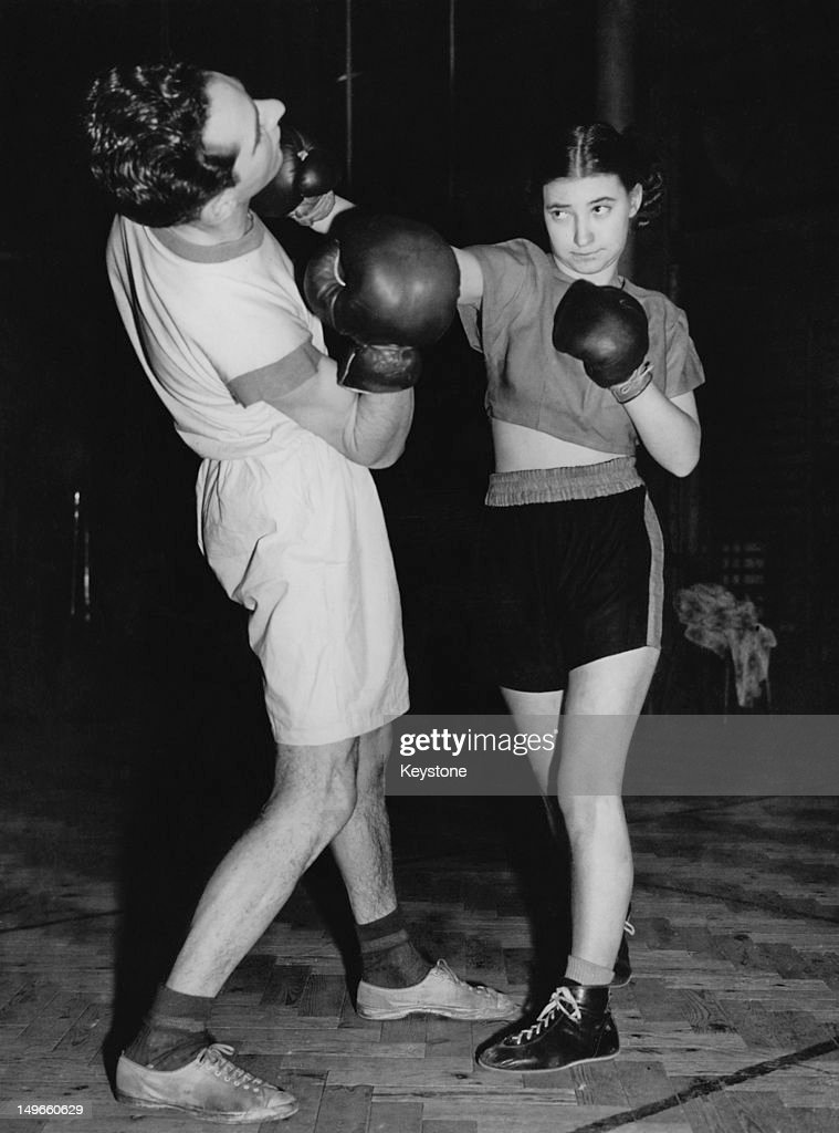 Eighteen year-old English boxer Barbara Buttrick (right) in training with a male sparring partner at Mickey Wood's Mayfair Gym, London, 4th February 1949. She is training for an exhibition bout at the Kilburn Empire, despite protests from leading figures in the boxing world, who are opposed to women's boxing. Buttrick went on to world championship titles in the flyweight and bantamweight classes, and later founded the Women's International Boxing Federation (WIBF).