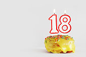 Eighteen  years anniversary. Birthday cupcake with white burning candles with red border in the form of number Eighteen. Light gray background with copy space