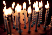 Birthday cake with lit candles including '18' candle