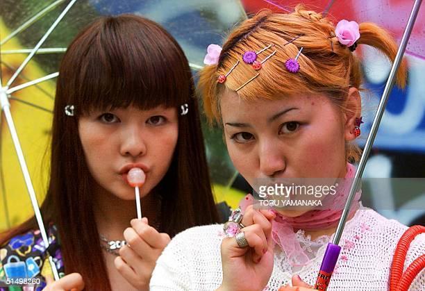 Eighteenyearold student Yoko Sasaki and her classmate Anna Shimasaki pose for pictures on a street at Tokyo fashion district Harajuku 17 June 2000...