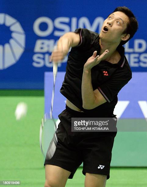 Eighthseeded Hu Yun of Hong Kong hits a smash during his first round match against B Sai Praneeth of India at the Japan Open 2013 badminton...