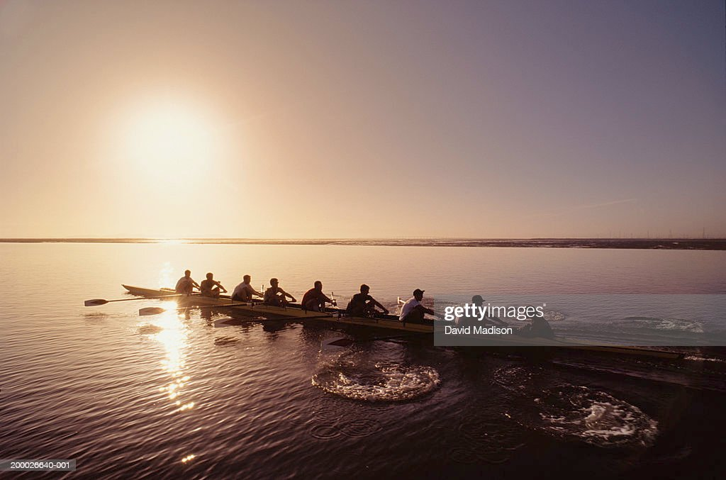 Eight-man crew rowing at sunrise, elevated view : Stock Photo