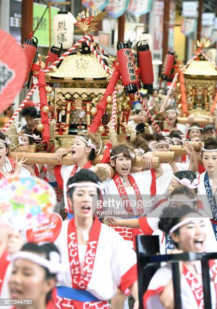 Eighty women aged from 15 to 30 carry two 200kilogram 'mikoshi' portable shrines on July 23 in the western Japan city of Osaka prior to the start of...