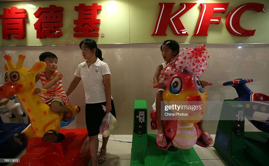 Eightyearold Chinese girl Zhang Huimin rides an electrical dinosaur in a KFC restaurant after a day's training on her way running from South China's...
