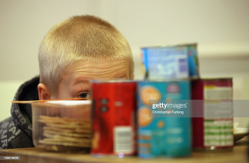 Eight-year-old Ryan Morris hides behind donated food for Christmas as his family collect essential provisions at Liverpool Foodbank on December 21, 2012 in Liverpool, England. With Christmas only days away, volunteers at the Central Liverpool Foodbank at the Frontline Trust, have seen one of their busiest days of the year as they give out free food for the needy. The centre has been giving out festive treats as well as its normal food donation - feeding over 1000 individuals in its first year, including over 300 children.