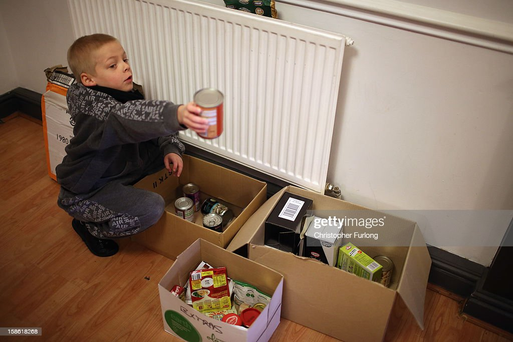 Eight-year-old Ryan Morris sifts through boxes of donated food for Christmas at Liverpool Foodbank on December 21, 2012 in Liverpool, England. With Christmas only days away, volunteers at the Central Liverpool Foodbank at the Frontline Trust, have seen one of their busiest days of the year as they give out free food for the needy. The centre has been giving out festive treats as well as its normal food donation - feeding over 1000 individuals in its first year, including over 300 children.