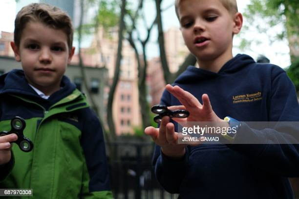 Eightyearold Tom Wuestenberg and his tenyearold brother Louis play with fidget spinners in a park in New York on May 23 2017 It was supposed to calm...