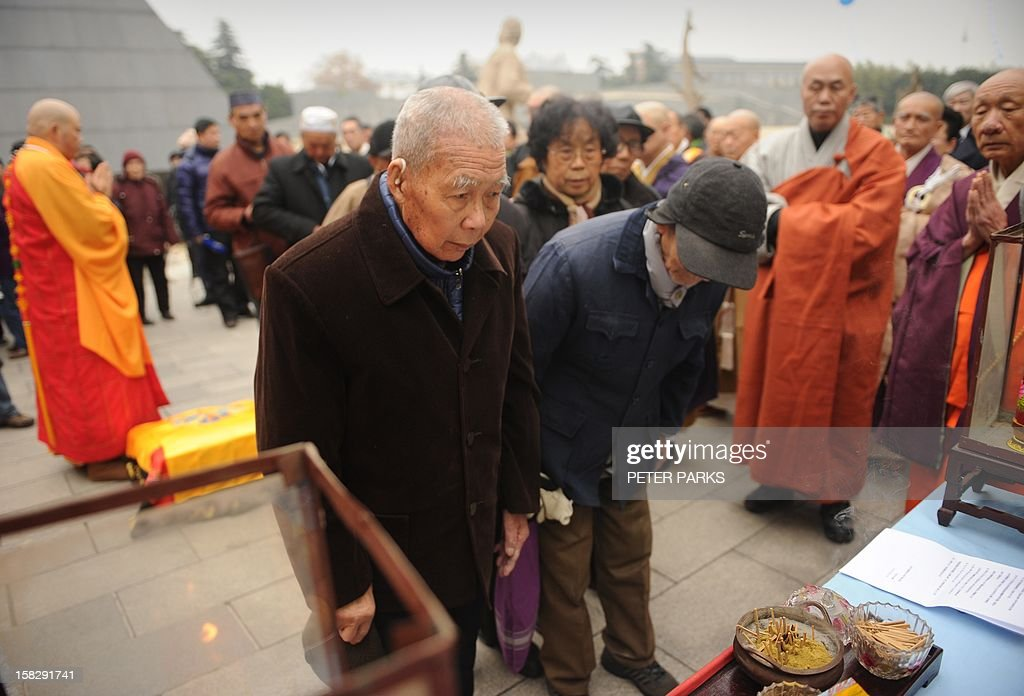 Eighty-eight-year-old Nanjing massacre survivor Li Gaoshan (centre L) pays his respects with other survivors to victims on the 75th anniversary of the Nanjing massacre at the Memorial Museum in Nanjing on December 13, 2012. Air raid sirens sounded in the Chinese city of Nanjing on December 13 as it marked the 75th anniversary of the mass killing and rape committed there by Japanese soldiers -- with the Asian powers' ties at a deep low. AFP PHOTO/Peter PARKS