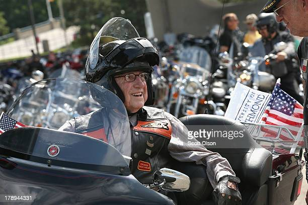 Eightyeightyearold WWII Marine Corps veteran Dr E Bruce Heilman takes a break on his motorcycle after riding in a parade through downtown to...