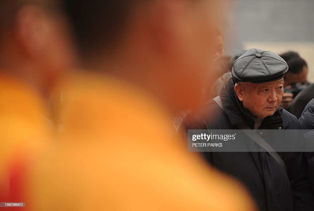 Eighty-seven-year-old Nanjing massacre survivor Li Zhong (R) stands next to Chinese Buddhist monks (L) at a ceremony for victims on the 75th anniversary of the Nanjing massacre at the Memorial Museum in Nanjing on December 13, 2012. Air raid sirens sounded in the Chinese city of Nanjing on December 13 as it marked the 75th anniversary of the mass killing and rape committed there by Japanese soldiers -- with the Asian powers' ties at a deep low. AFP PHOTO/Peter PARKS