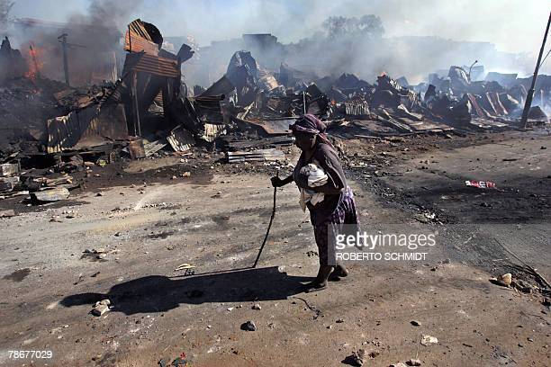 Eightyyearold Thabita holds her cat the only possesion she was able to save from a fire as she walks past still burning remains of a block of stores...