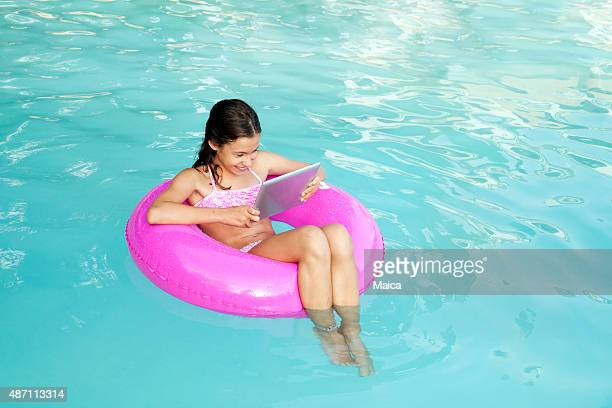 Eigth years old reading a book in a swimming pool