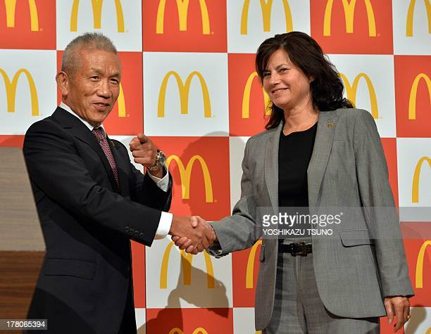 Eiko Harada fastfood giant McDonald's Japan president and chairman shakes hands with the company's new president and CEO Sarah Casanova at a press...
