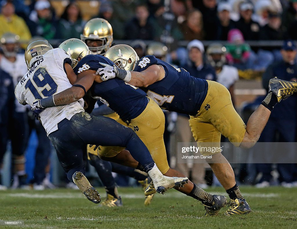 Eilar Hardy and Carlo Calabrese of the Notre Dame Fighting Irish sack Keenan Reynolds of the Navy Midshipmen at Notre Dame Stadium on November 2 2013...