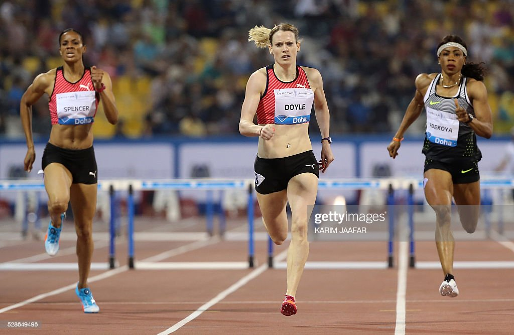 Eilidh Doyle (C) of Great Britain crosses the finish line to win the women's 400 metres hurdles final as Bahrain's Kemi Adejoya (R) comes in second place and Jamaica's Kaliese Spencer in third place at the Diamond League athletics meeting at the Suhaim bin Hamad Stadium in Doha on May 6, 2016. / AFP / KARIM