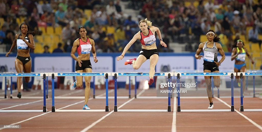 Eilidh Doyle of Great Britain celebrates (C) runs win the women's 400 metres hurdles final as Bahrain's Kemi Adejoya (2R) comes in second place and Jamaica's Kaliese Spencer (2L) in third place and America's Cassandra Tate (L) in fifth place at the Diamond League athletics meeting at the Suhaim bin Hamad Stadium in Doha on May 6, 2016. / AFP / KARIM