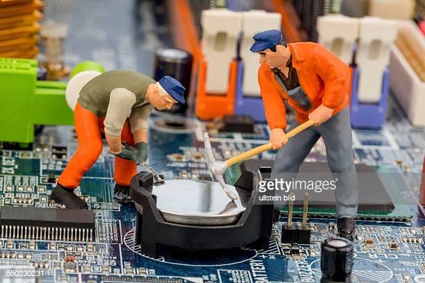 Ein Arbeiter repariert die Platine eines Computers Symbolfoto für Datensicherheit