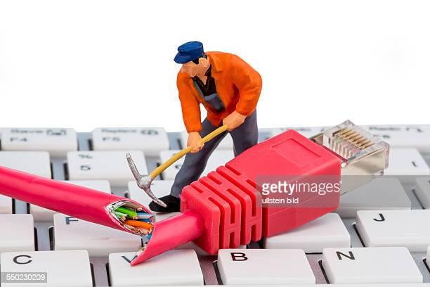 Ein Arbeiter repariert ein Netzwerkkabel Symbolfoto für Datensicherheit