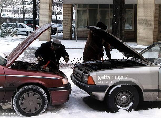 Ein Autofahrer gibt dem anderen Starthilfe Aufladen der Batterie Dezember 1996