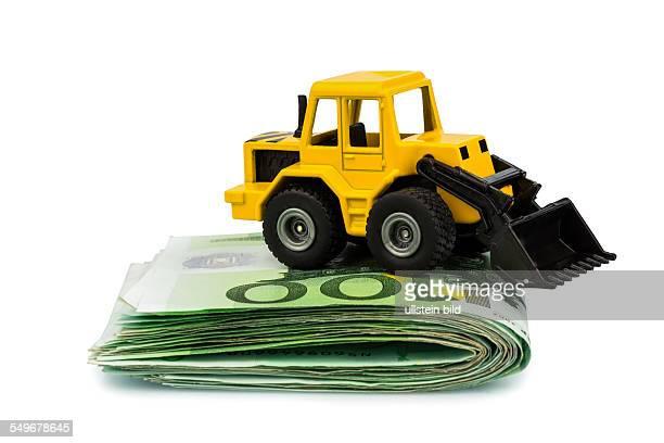 Ein Bagger steht auf Eurogeldscheinen Symbolfoto für Kosten Erträge und Förderungen im Baugewerbe und der Bauwirtschaft