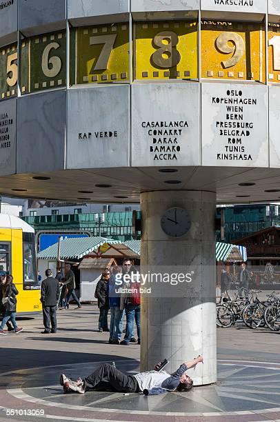 Ein Betrunkener unter der Weltzeituhr auf dem Alexanderplatz in BerlinMitte