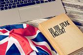 Ein Computer, Flagge von Großbritannien und Buch mit dem Titel Sprechen Sie englisch