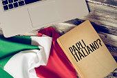 Ein Computer, Flagge von Italien und Buch mit dem Titel Sprechen Sie italienisch