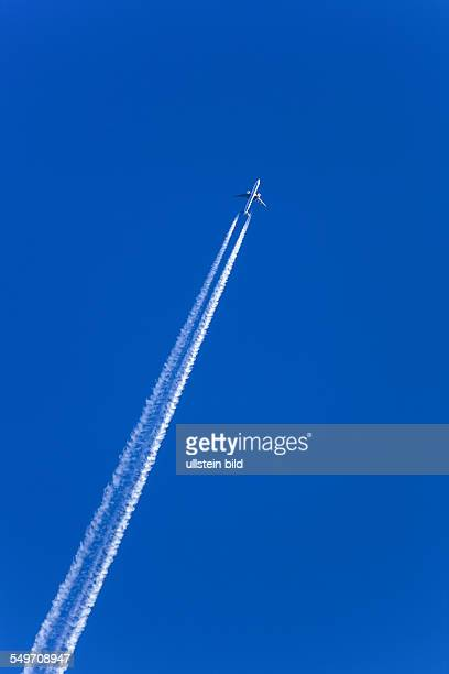 Ein Flugzeug mit Kondensstreifen am blauen Himmel Smog und Luftverschmutzung