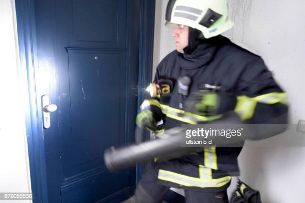 Ein GastFeuerwehrmann bei der Berliner Feuerwehr aus Frankfurt/Oder öffnet zur Kontrolle mit einer Ramme eine Wohnung während eines Wohnungsbrandes...