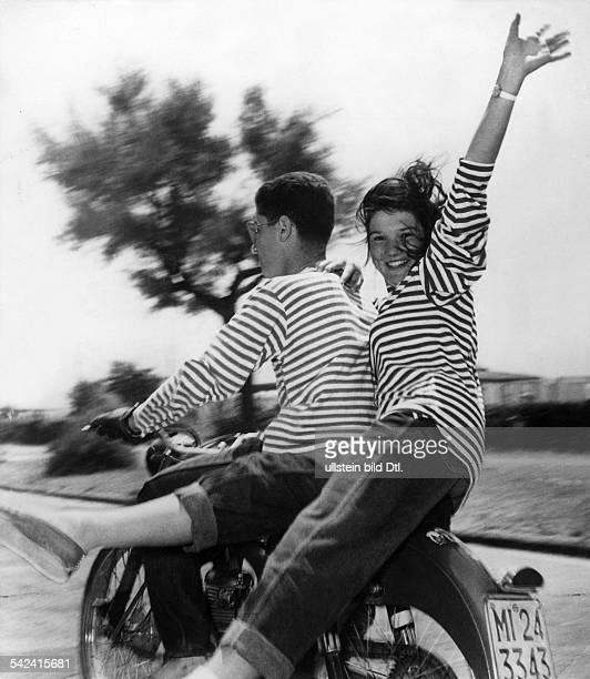 Ein junges Paar in modisch gestreiften TShirts fährt Motorrad 50er Jahre