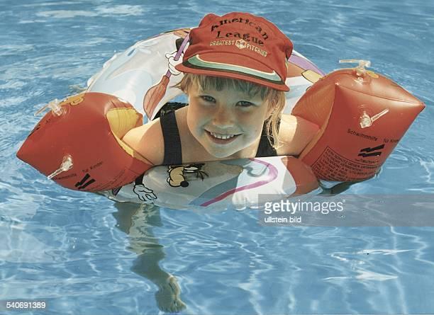 Ein Kind hängt in einem Schwimmreifen an beiden Armen trägt sie Schwimmflügel und auf dem Kopf eine Schirmmütze Sicherheit Undatiertes Foto