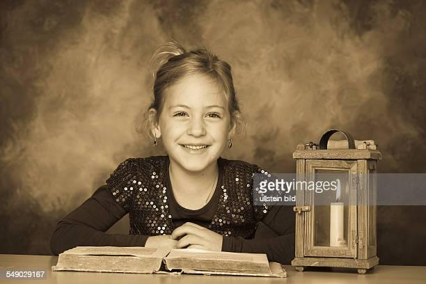 Ein Kind mit Buch und Laterne in der Adventzeit