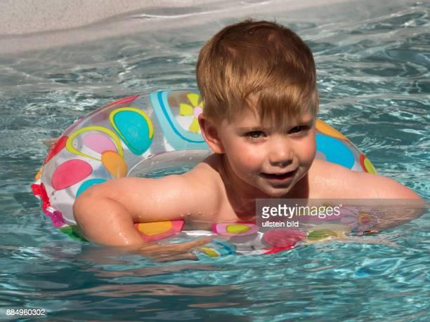 Ein Kind schwimmt mit einem Schwimmreifwn im Pool und kühlt sich an einem heißen Sommertag ab
