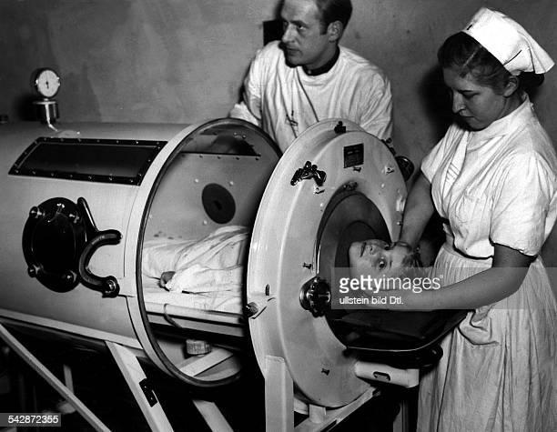 ein Kind wird vom Arzt und einerSchwester zur Behandlung von Polio inder Eisernen Lunge vorbereitet dieseist ein Geschenk der `American Friendsof...