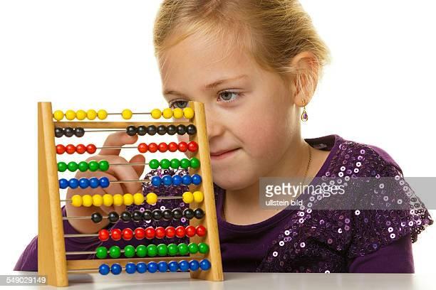 Ein kleines Schulkind rechnet mit einem Abakus