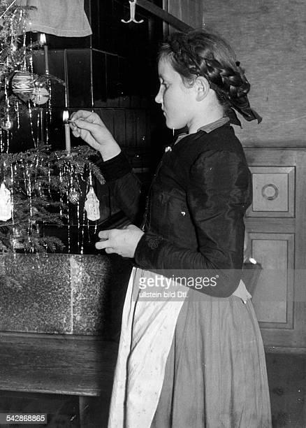Ein Maedchen in sueddeutscher Tracht zuendeteine Kerze am Weihnachtsbaum an Foto Karl Mueller Freiburg / Breisgau veröff 1940