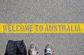 Ein Mann mit einem Koffer steht an der Grenze zu Australien