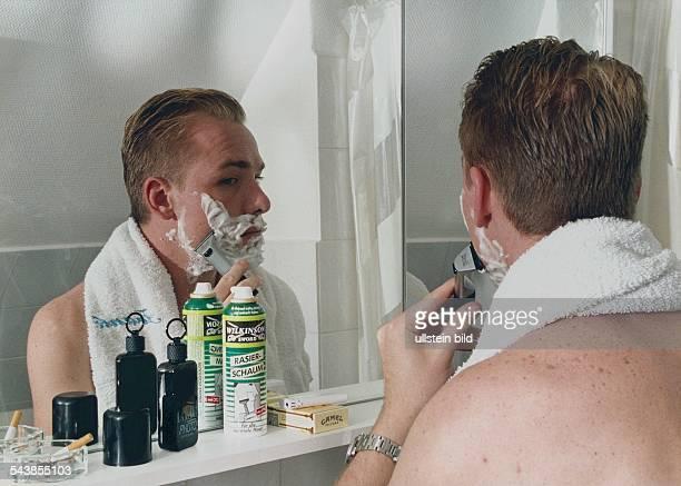 Ein Mann steht vor einem Badezimmerspiegel und rasiert mit einer Klinge seine mit Rasierschaum eingeseiften Wangen Auf der Badezimmerkonsole stehen...