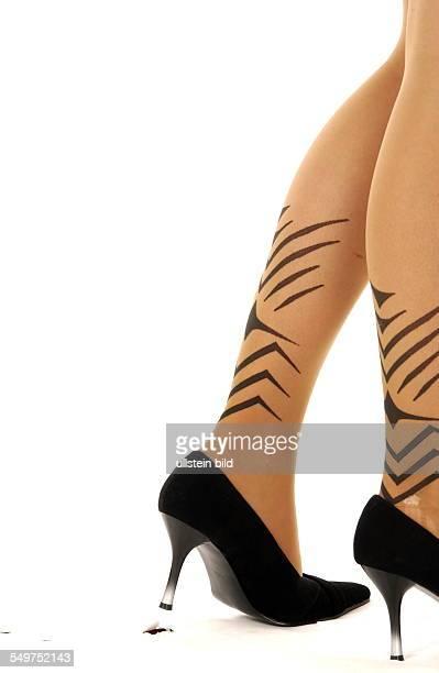 Ein Model verursacht mit dem Absatz ihrer Schuhe ein Loch im Papierhintergrund