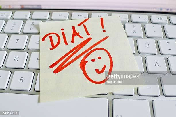 Ein Notizzettel liegt auf der Tastatur eines Computers zur Erinnerung Diät