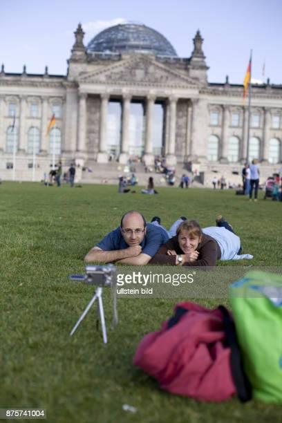 Ein Paar liegt auf der Wiese vor dem Reichstag und wartet auf eine Aufnahme mit Selbstausloeser Freizeit Hobby Tourismus Regierungsviertel Tourist...