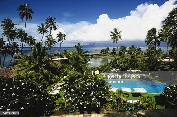 Ein Swimmingpool mit Liegestühlen und Sonnenschirmen umgeben von Palmen und exotischen Pflanzen in einer Hotelanlage in Papeete auf Tahiti in der...