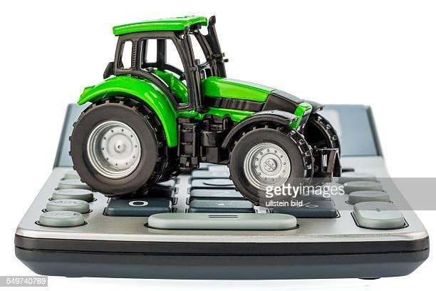 Ein Traktor liegt auf einem Taschenrechner Kosten für Benzin Abnutzung und Versicherung Kosten und Förderungen in der Landwirtschaft