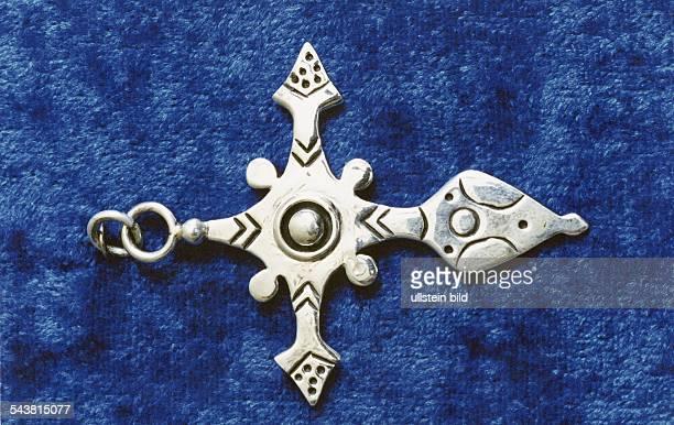 Ein Tuaregkreuz oder auch Agadezkreuz Ein kreuzförmiger mit Einkerbungen versehener Anhänger aus Silber ein in der Sahararegion Westafrikas weit...
